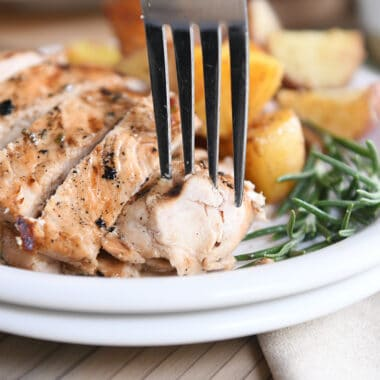 fork taking piece of rosemary ranch chicken on white plate with rosemary and potatoes