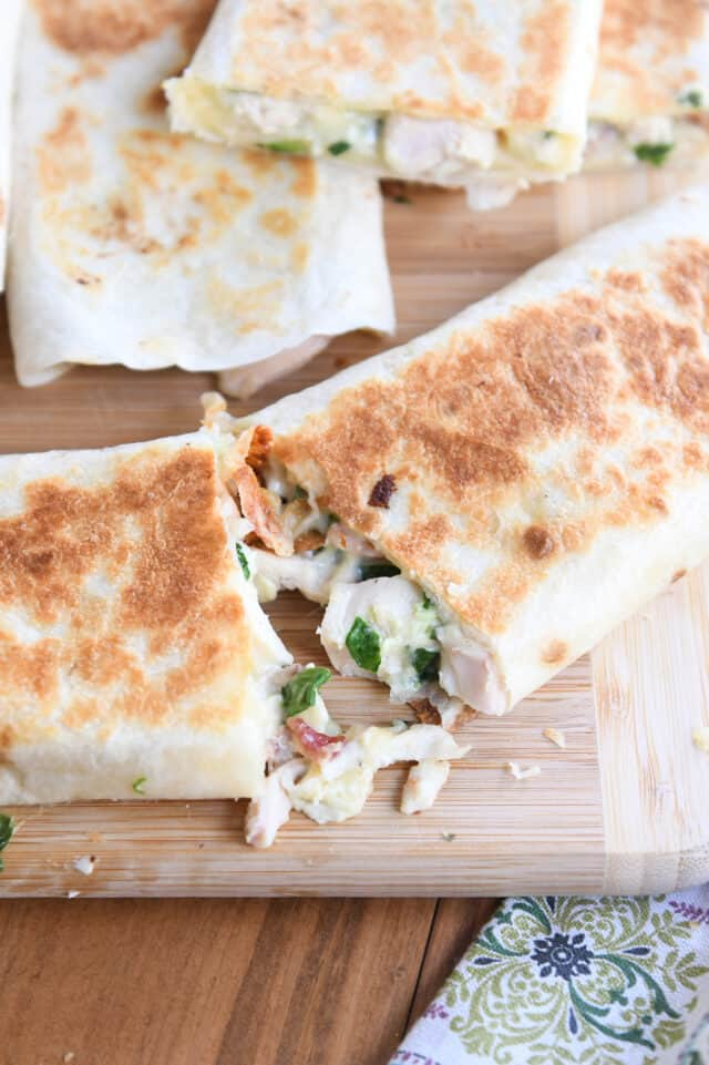 two halves pulling apart of crispy chicken bacon ranch wrap on wood cutting board
