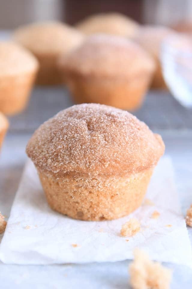 cinnamon sugar doughnut muffin on white napkin with crumbs around napkin