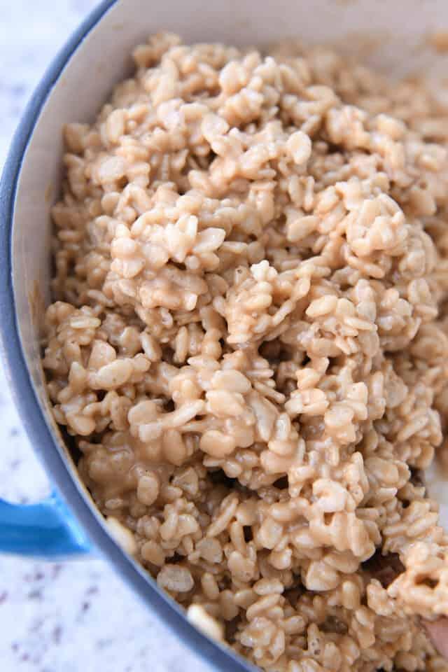 blue cast iron pan with rice krispie peanut butter mixture