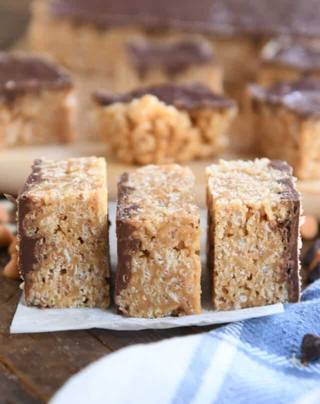 three scotcheroo bars stacked side by side on white parchment paper