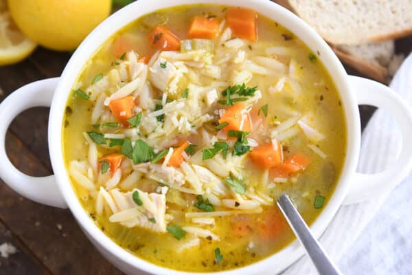 white bowl with handles filled with lemon chicken orzo soup