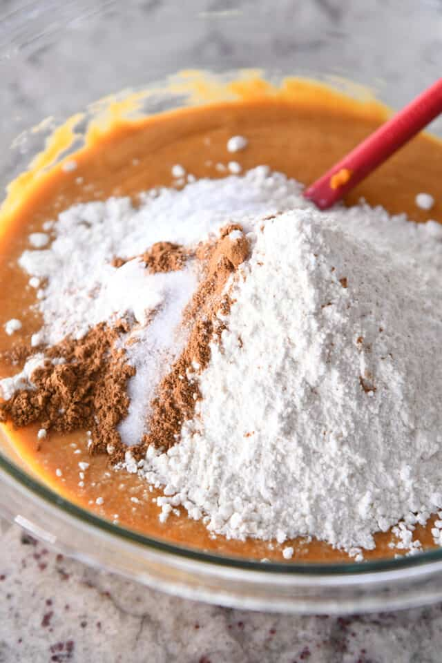 adding flour, cinnamon and salt to wet ingredients for pumpkin muffin batter in glass bowl