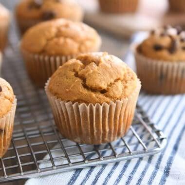sourdough pumpkin muffin in brown paper liner on metal cooling rack