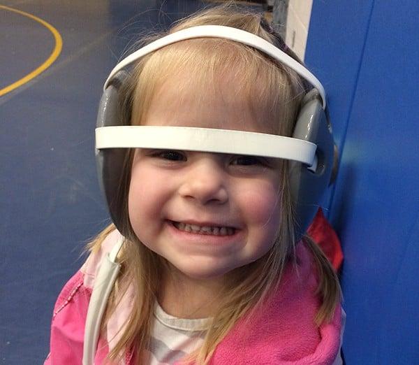 A little girl with wrestling headgear on.