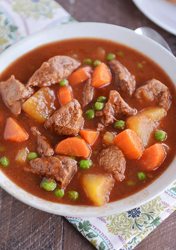 A bowl full of stew filled with cubes of beef, carrots, peas, and potatoes.