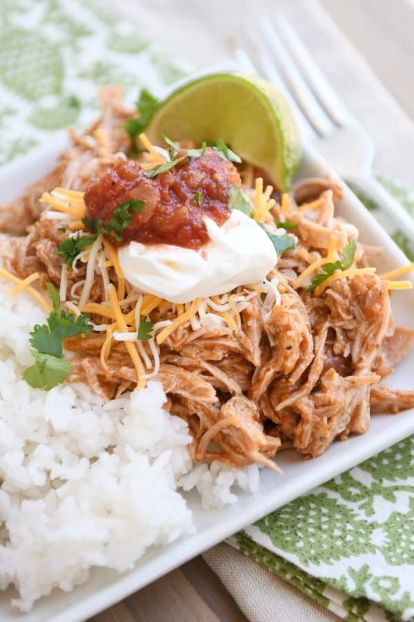 Instant pot Mexican pork on white tray with rice and beans and sour cream, salsa, and fresh limes.
