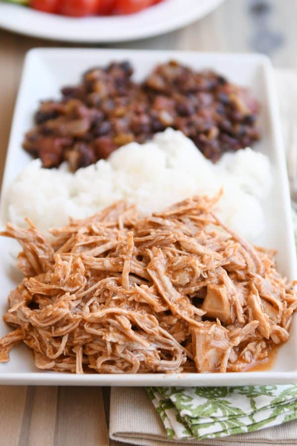 Instant pot Mexican pork on white tray with rice and beans.