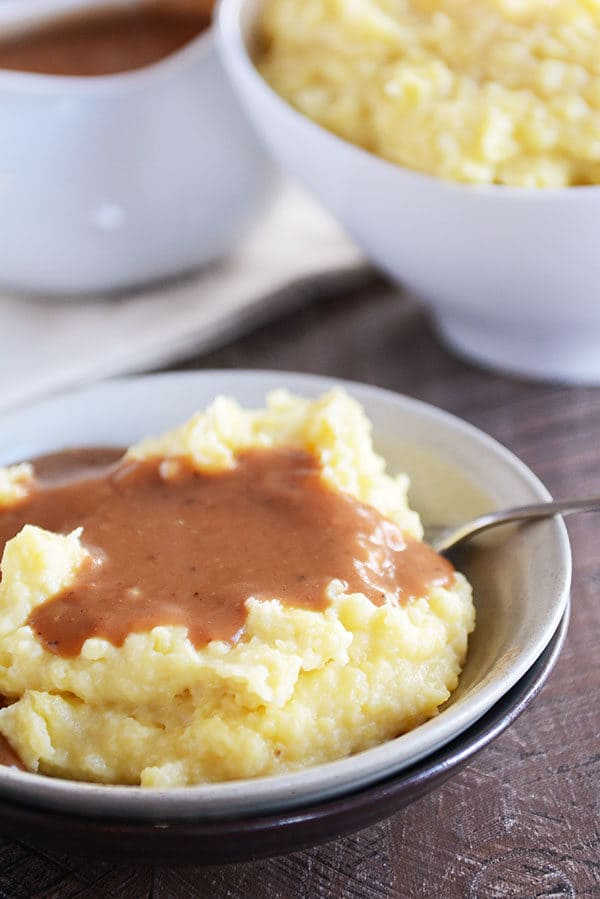 A bowl full of mashed potatoes topped with brown gravy.