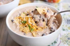 Instant Pot white chicken chili in white bowl with spoon and shredded cheese.