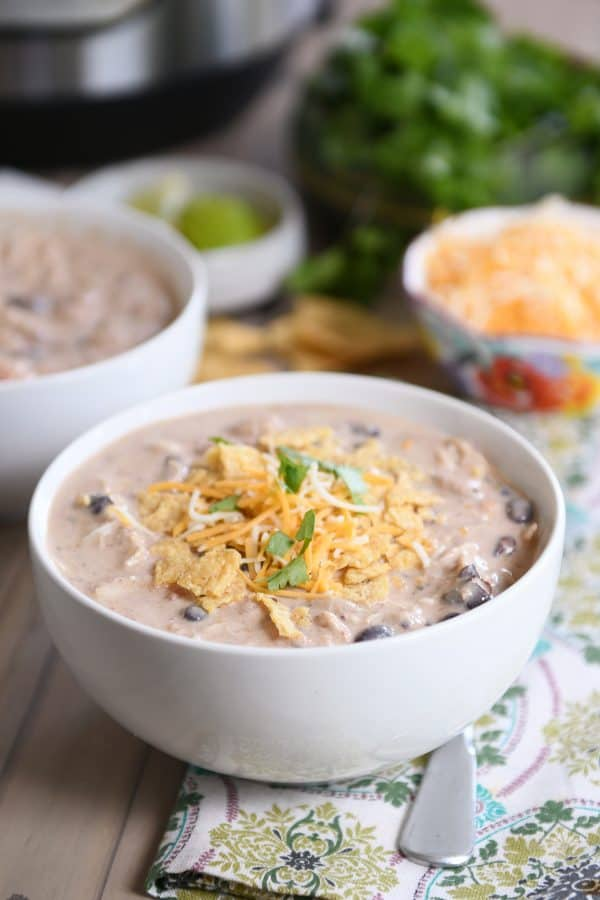 Instant Pot white chicken chili in white bowl and shredded cheese.