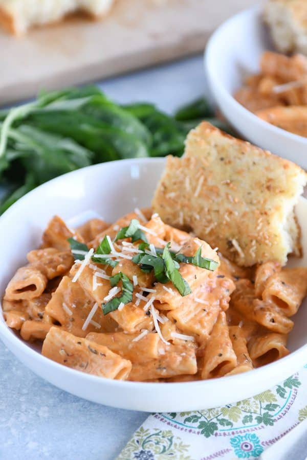 White bowl with Instant Pot creamy baked ziti and piece of focaccia bread.