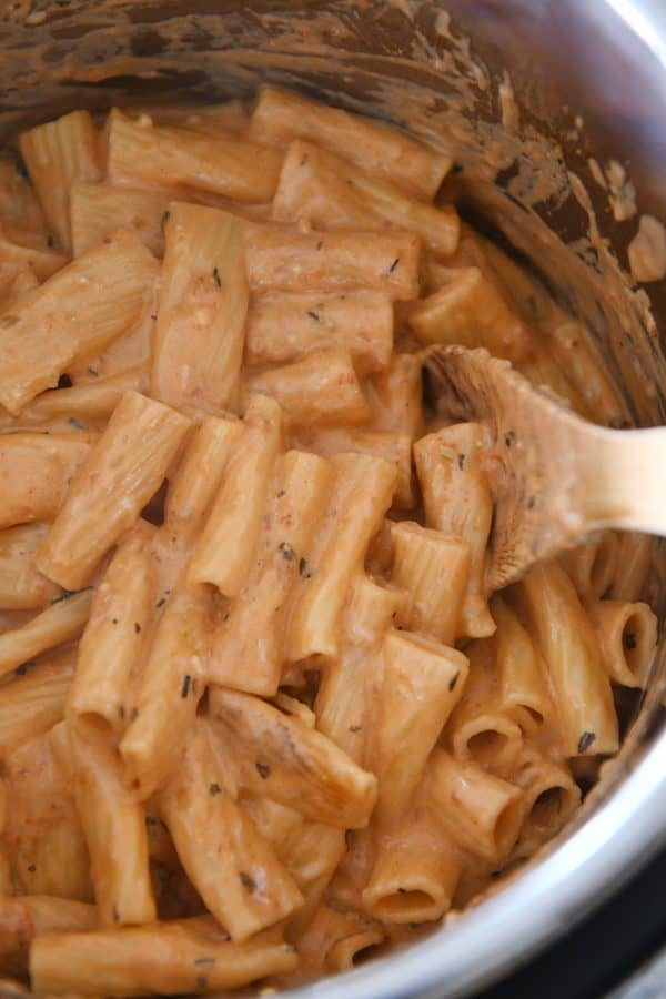 Stirring Instant Pot creamy baked ziti with metal spoon.