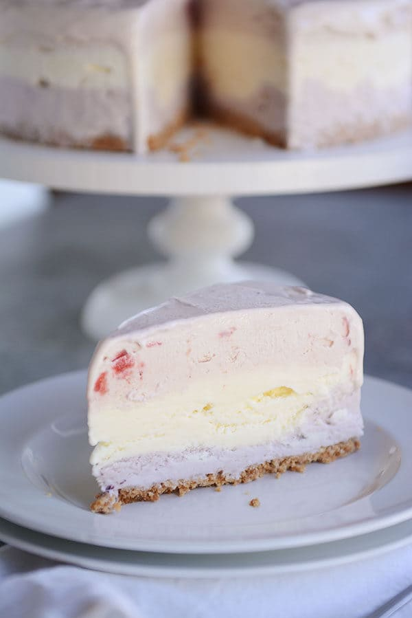 A slice of layered ice cream cake with a sugar cone crust on a white plate.
