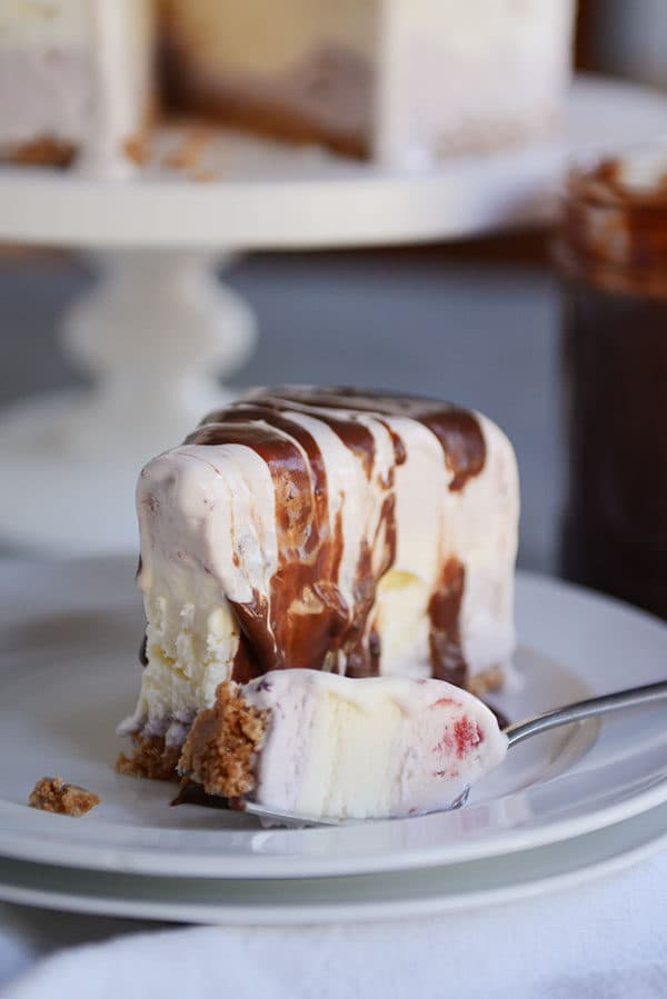 A slice of ice cream cake with a bite taken out on a white plate.