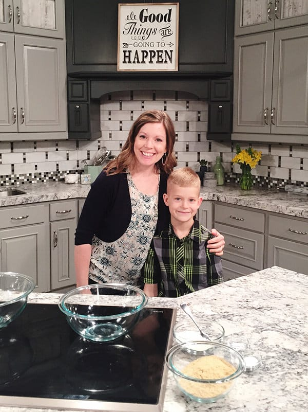 Mel from Mel's Kitchen Cafe and her son standing in a kitchen set for a TV Segment.