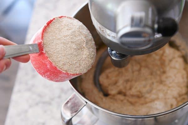 whole wheat flour getting poured into a metal KitchenAid bowl