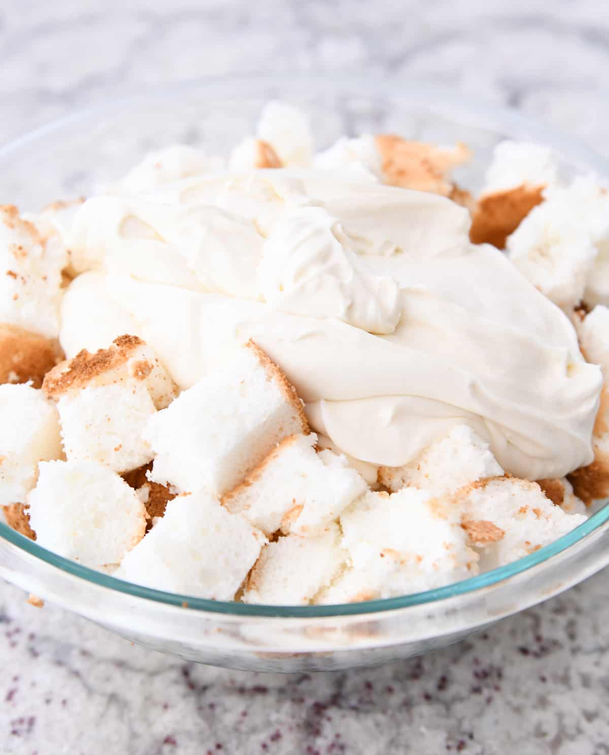 Bowl of angel food cake pieces and cream poured on top.