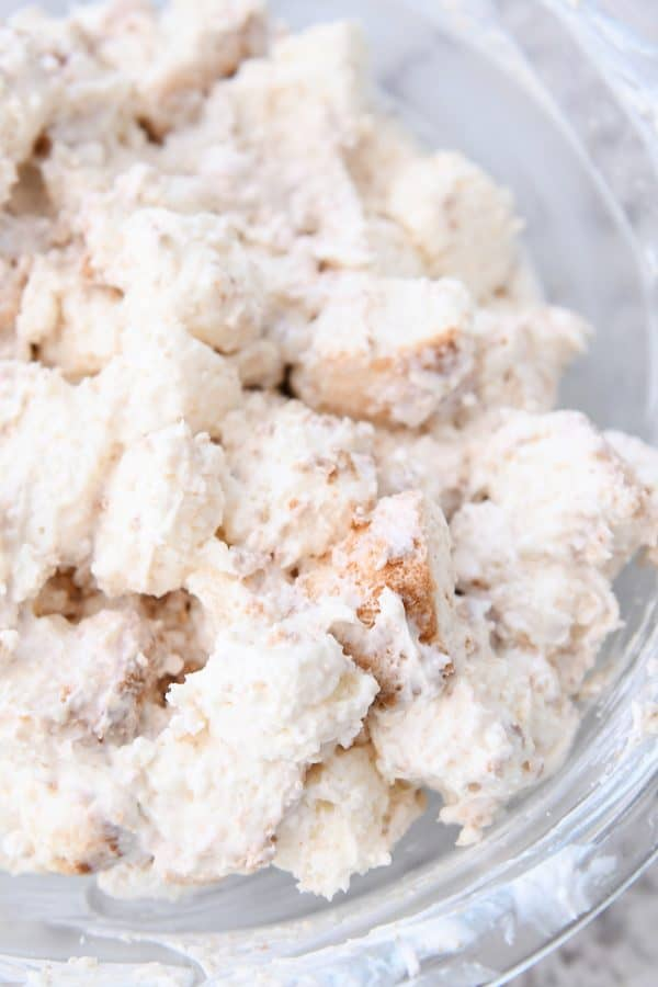 Glass bowl of cream coated angel food cake pieces.