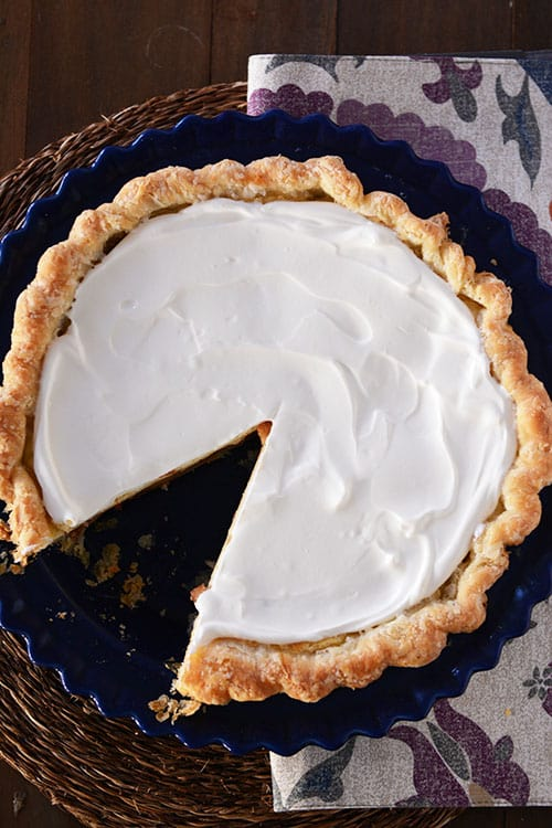 Top view of a whipped cream topped pie with a slice cut out.