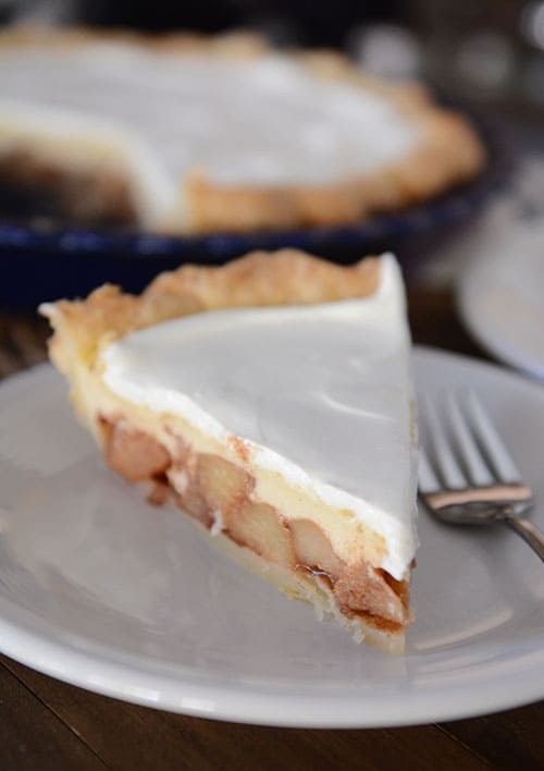 A slice of apple pie with a cheesecake and whipped cream layer on a white plate.