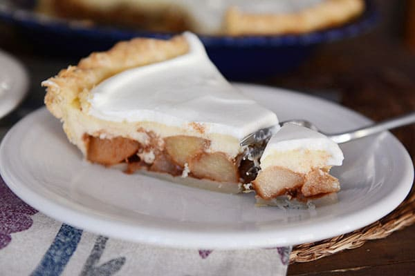A slice of apple cheesecake pie with a bite being taken out.