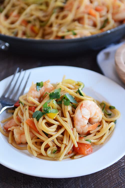 A white plate full of spaghetti noodles with vegetables and shrimp.