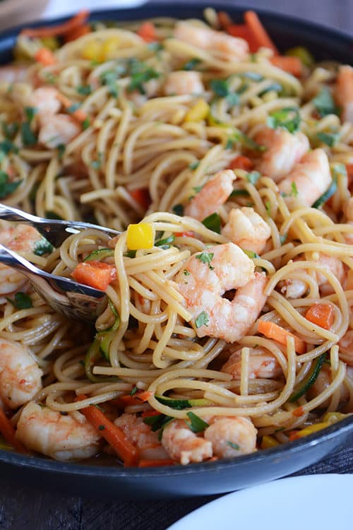 A skillet full of spaghetti noodles, shrimp, and chopped vegetables.