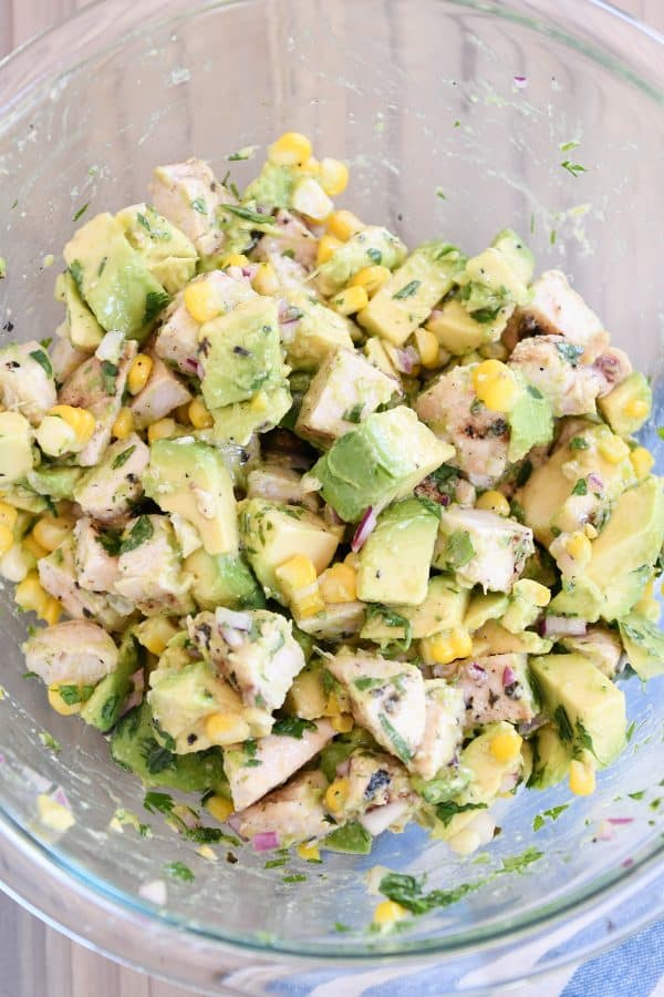 Avocado chicken salad all mixed up in glass bowl.