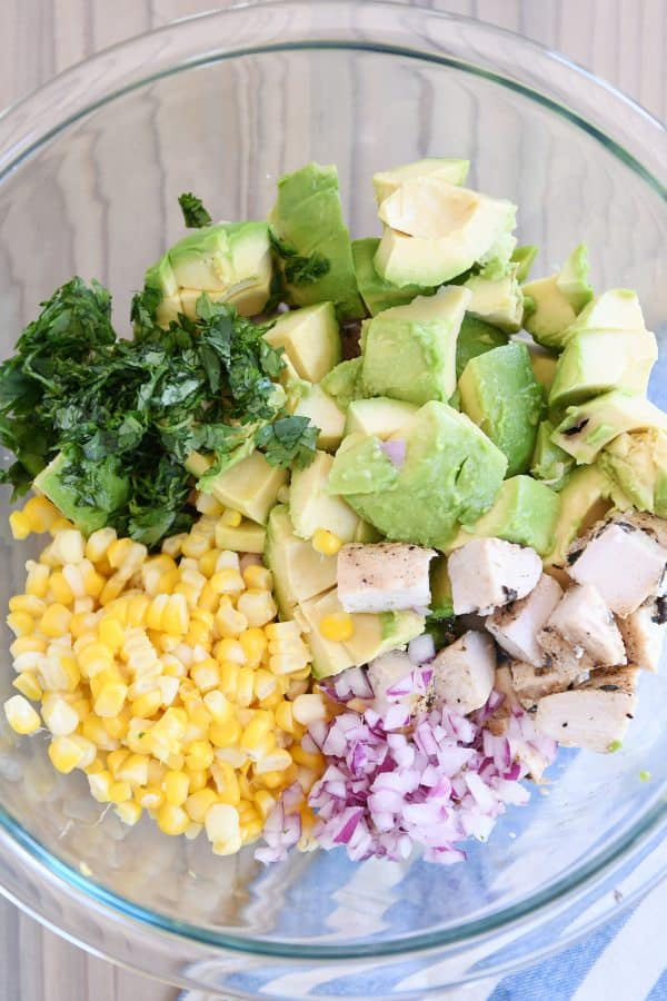 Avocado chicken salad ingredients - cilantro, avocado, corn, onion, chicken - in glass bowl.