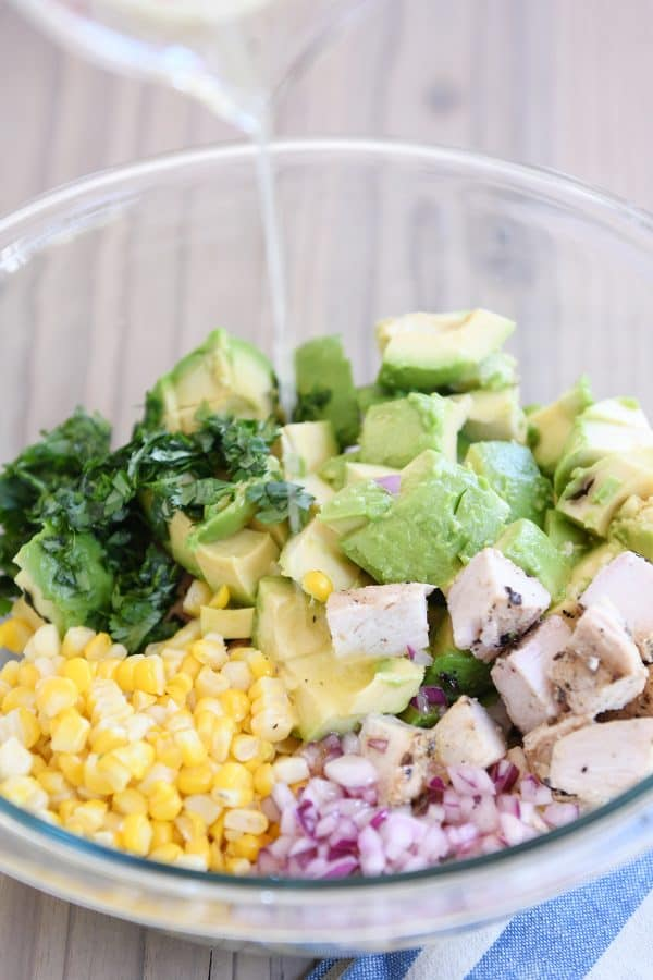 Pouring lemony dressing over avocado chicken salad in glass bowl.