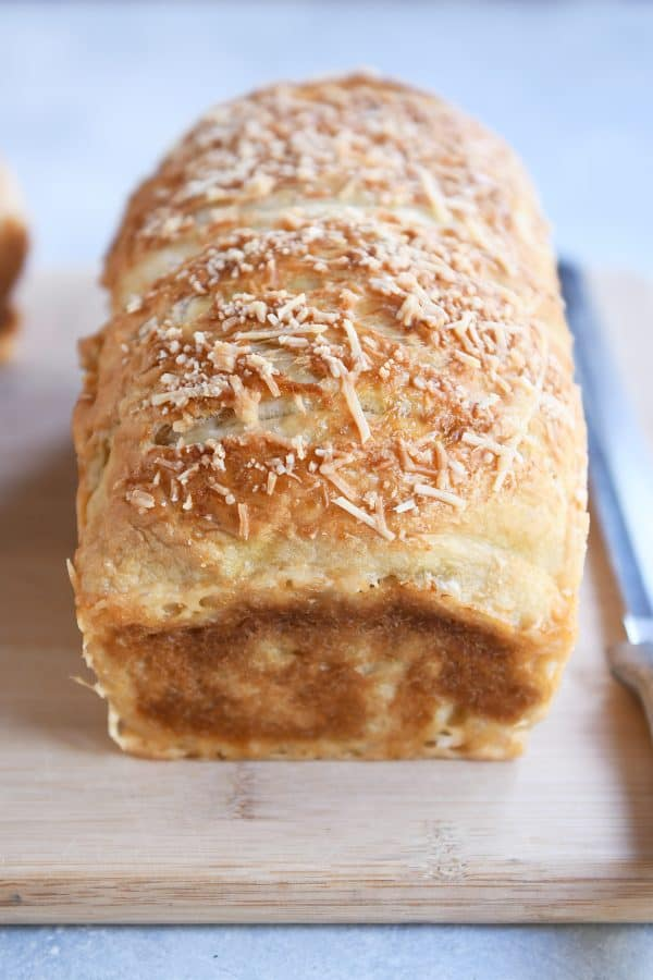 Loaf of parmesan bagel bread on wood cutting board.
