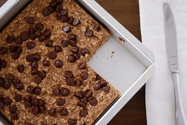 Top view of a square pan of banana oat chocolate chip bars with a piece cut out.