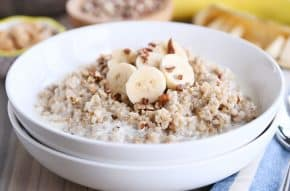 White bowl filled with Instant Pot banana bread steel cut oats with sliced bananas and milk.