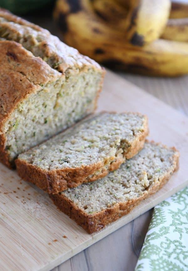 Loaf of sliced zucchini banana bread on wood cutting board.