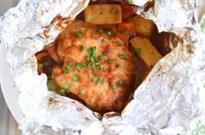 BBQ Hawaiian chicken foil packet opened with chicken, peppers and pineapple inside.