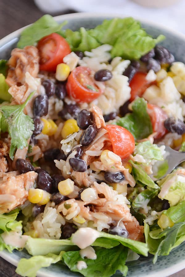 A chicken, rice, black bean, and veggie mixture served over lettuce in a white bowl.