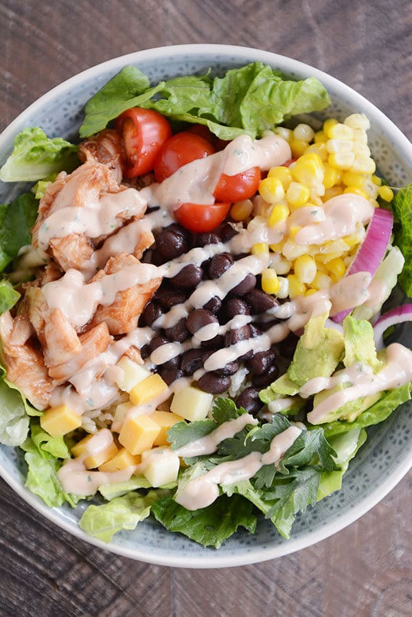 Top view of a BBQ chicken, black bean, and vegetable salad drizzled with dressing.