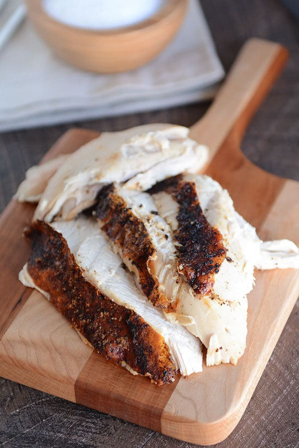 A small wooden cutting board with thick slices of roast chicken on top.