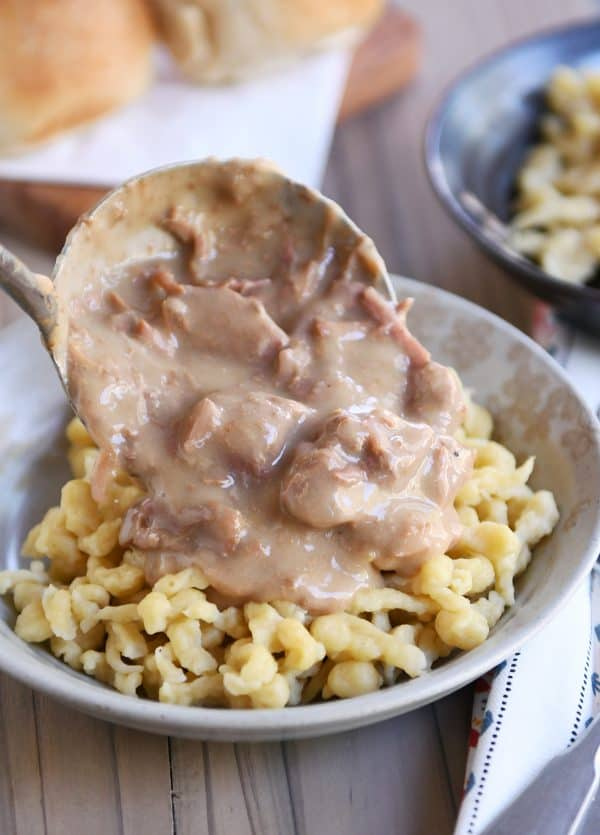 Pouring slow cooker beef stroganoff over spaetzle noodles.