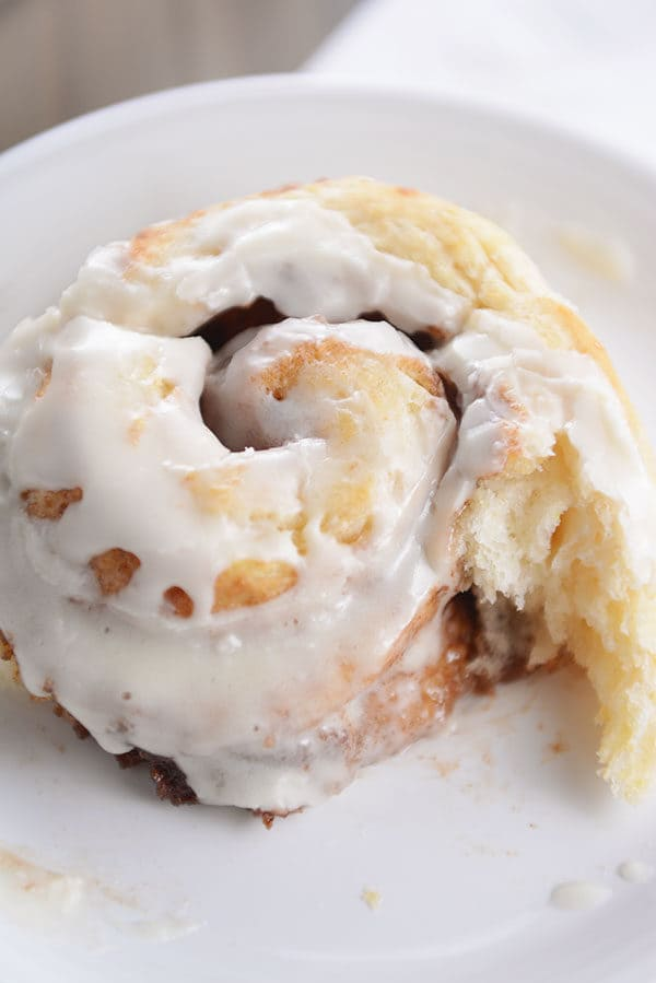 A frosted cinnamon roll with a bite taken out on a white plate.