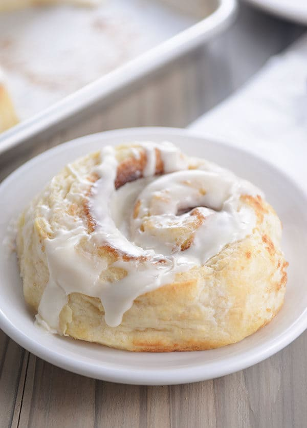 A frosted cinnamon roll on a small round white plate.