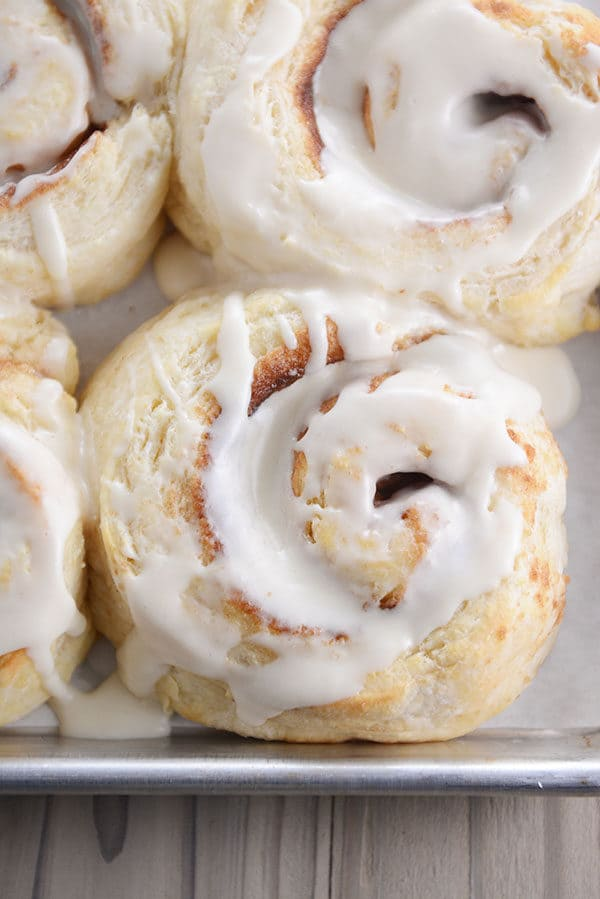 Top view of a frosting-topped biscuit cinnamon rolls on a cookie sheet.
