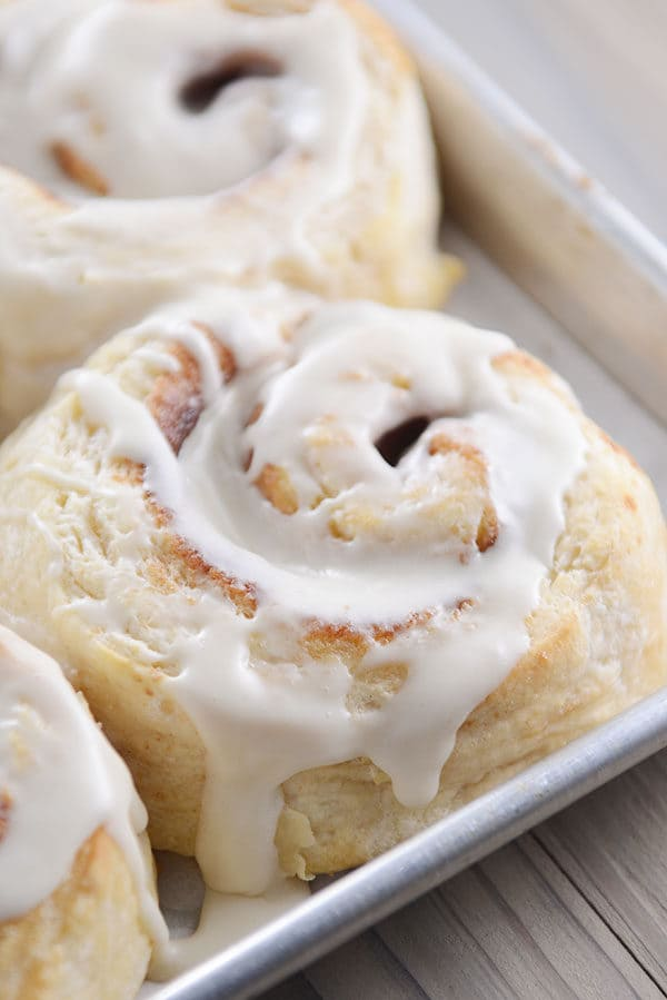A cookie sheet full of frosted cinnamon rolls.