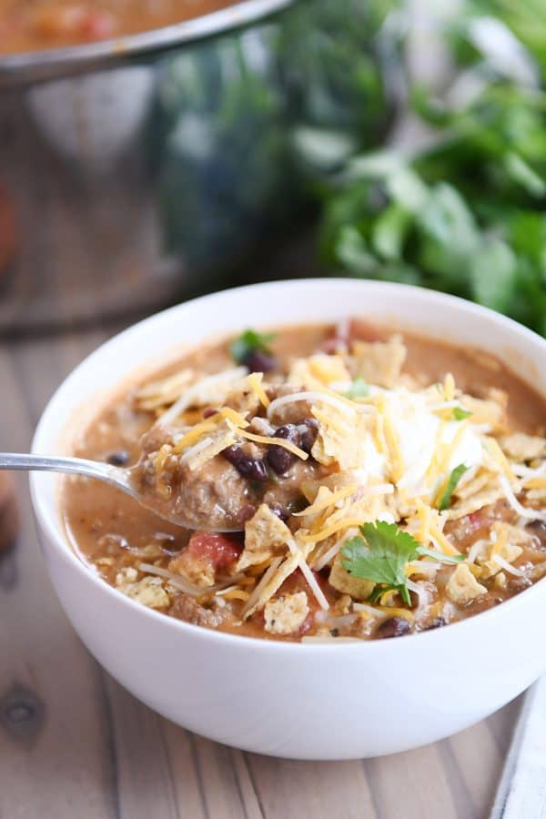 A spoon taking a bite of creamy black bean taco soup with sour cream and cheese on top out of the bowl.