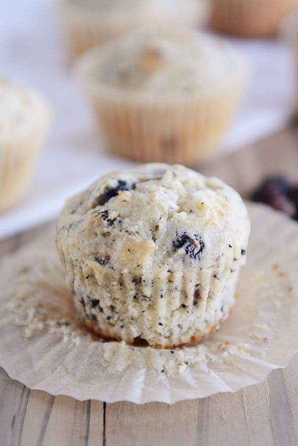 An unwrapped blueberry muffin sitting on the liner.
