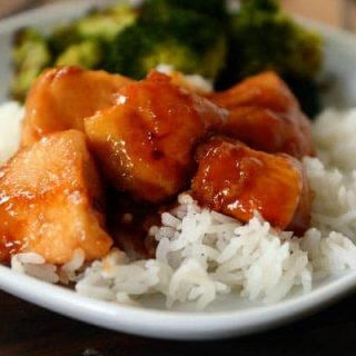 pieces of sauce-covered chicken sitting on white rice