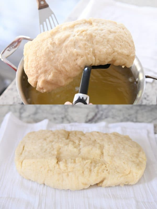 a spatula lifting a loaf of bagel bread out of a pot of water