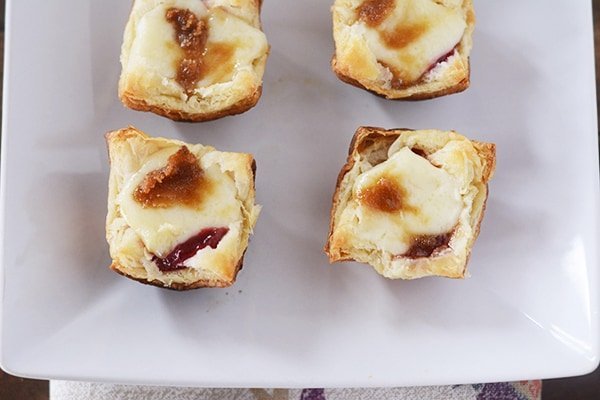 Top view of four puff pastry baked brie bites.