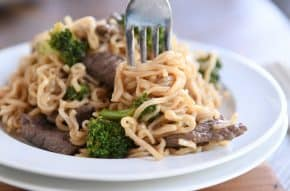 Twisting ramen noodles on fork with beef and broccoli on white plate.